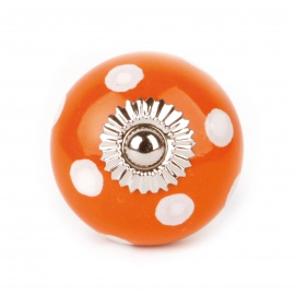 Kleiner oranger Möbelknauf mit weißen Punkten
