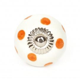 Kleiner weißer Möbelknauf mit orangen Punkten